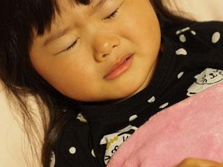 苦しそうに目を閉じる幼児
