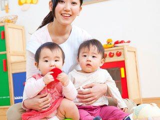 保育園で保育士に抱かれる幼児