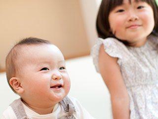 お姉ちゃんの傍で笑う赤ちゃん