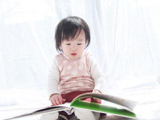 絵本を開いて見入る幼児
