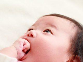 自分の手を咥える赤ちゃん