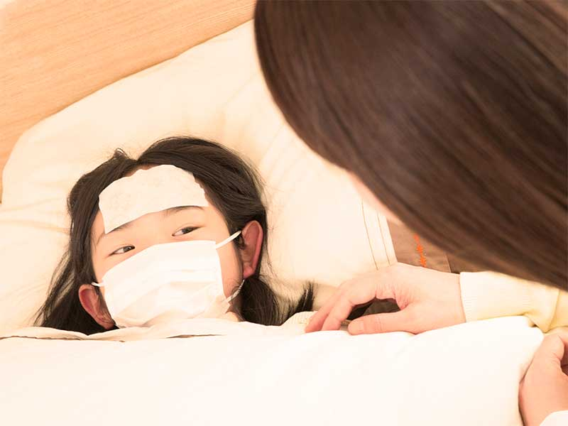 母親に看病されマスクをして布団に寝ている女の子