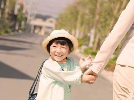 母親に手を引かれ笑顔で登園している保育園児
