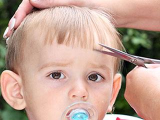 男の子の前髪をはさみで切る