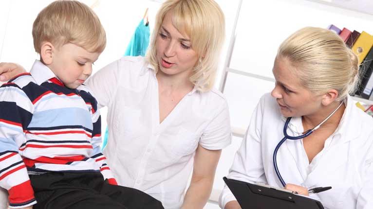 病院で女性医師からの診察を受けている外国人の子供と付き添いの母親