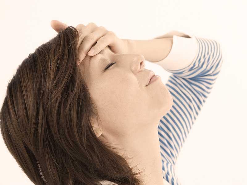 熱が出て額に手を当てている女性