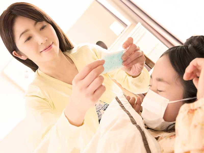 マスクをして布団に寝ている女の子に冷えピタシートを貼ってあげる母親