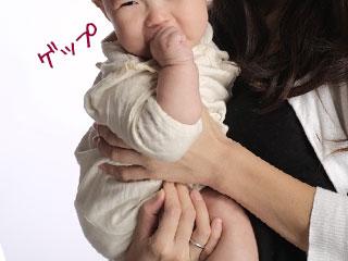腕に赤ちゃんを座らせて抱っこする母親
