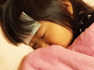 額に熱さましシートを貼って寝る子供