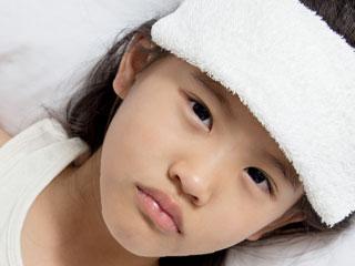 額にタオルを載せた少女