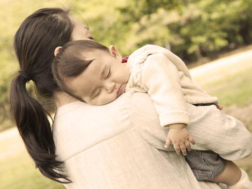 子供を抱っこしている女性の後姿