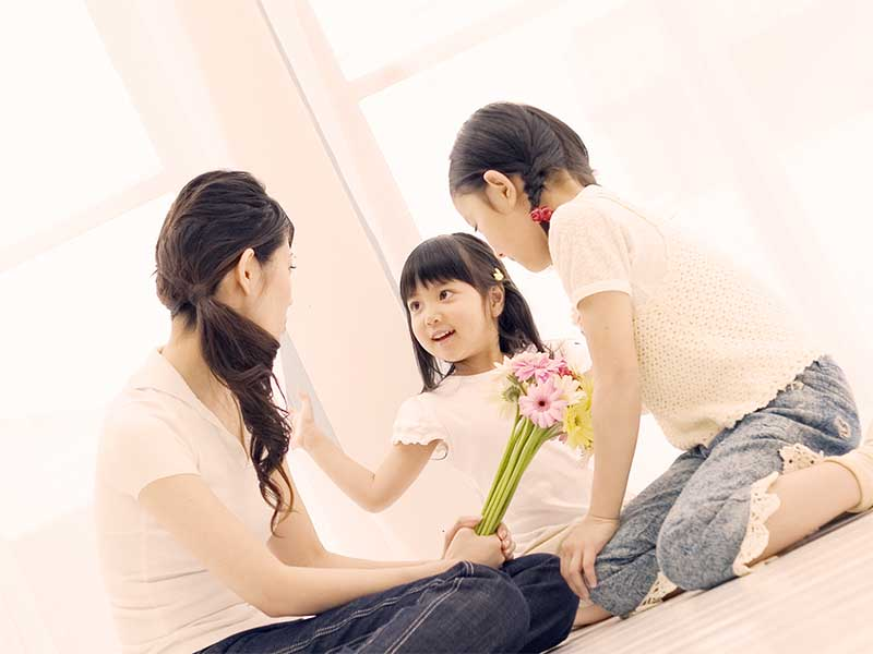 小さな姉妹と遊んでいる母親