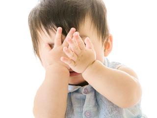手で顔を隠す赤ちゃん