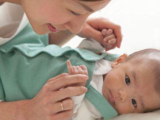 赤ちゃんの手を掴んで話しかける母親