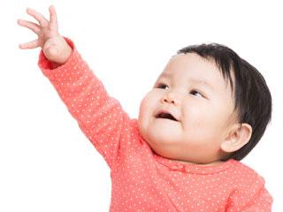 片手を伸ばす赤ちゃん