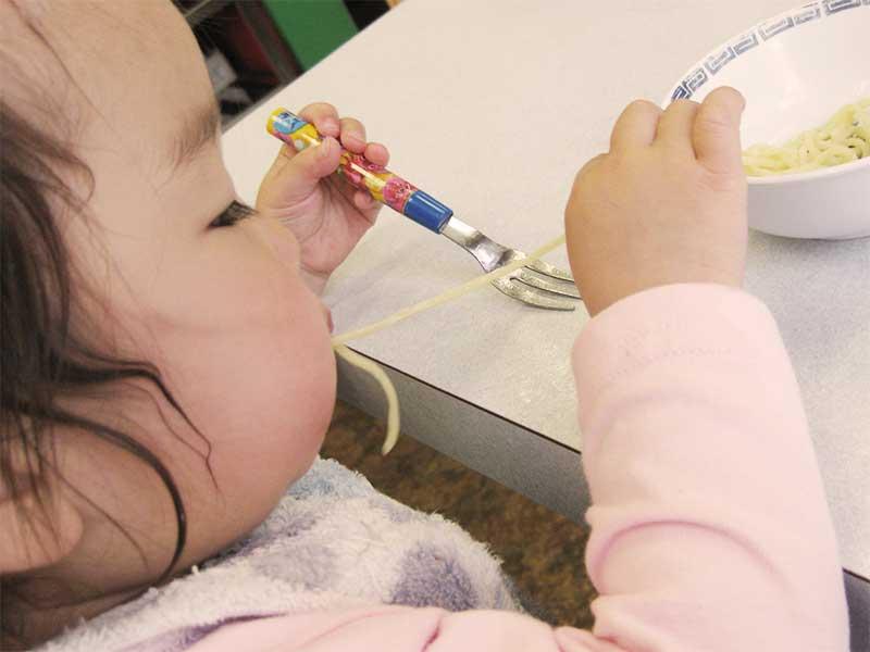 自分でパスタを食べている赤ちゃん