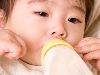 哺乳瓶を咥えて吸い込む赤ちゃん
