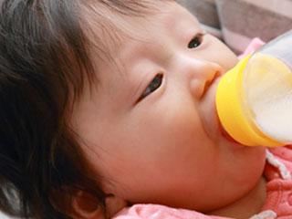 飲みながら哺乳瓶を見つめる赤ちゃん