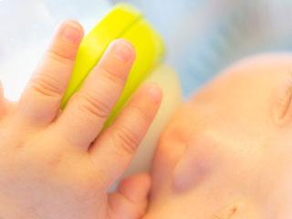 哺乳瓶に手を当てて飲む赤ちゃん