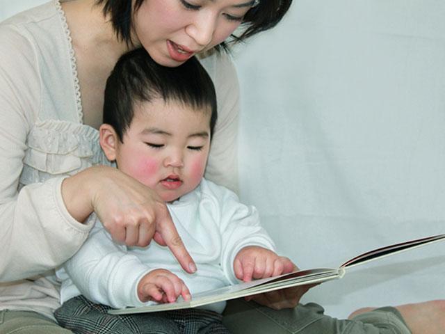 幼児に本を見せながら教える母親