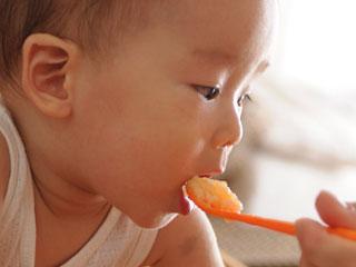 スプーンで擦った野菜を食べる赤ちゃん