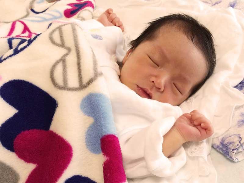清潔な布団で寝ている新生児