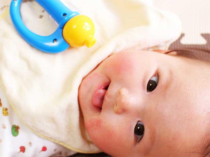 湿疹でほっぺが少し赤くなってるけど笑顔の新生児