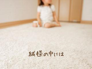 絨毯を引きつめた部屋に座る子供