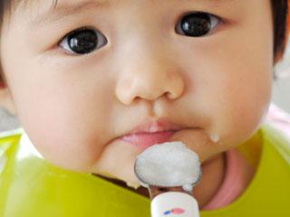 お粥をスプーンで食べる赤ちゃん