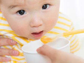 スプーンの離乳食を食べようとする赤ちゃん