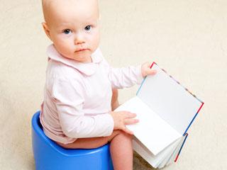 おまるに座りながら本をめくる赤ちゃん