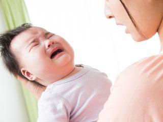 泣く赤ちゃんを見つめる母親