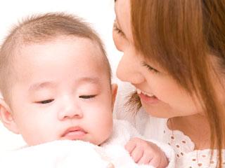 赤ちゃんの耳元で話しかける母親