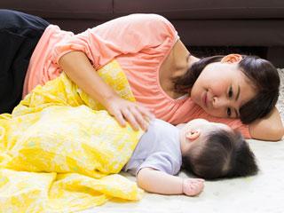 赤ちゃんの傍で一緒に横になる母親