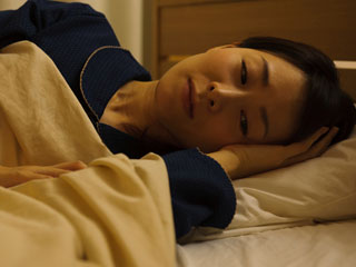 暗い寝室で静養する女性