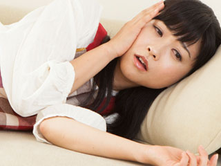 ソファに横になって休む女性