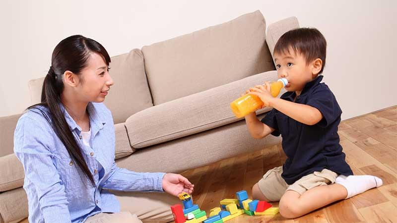 部屋の中で母親とブロックで遊んでいる男の子