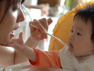 ママに離乳食を食べさせるもらう赤ちゃん