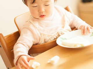 テーブルの上に落ちたパンを掴もうとする赤ちゃん