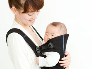 抱っこ紐で赤ちゃんを運ぶお母さん