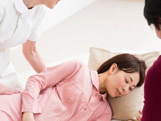 横になる妊婦と世話する看護師