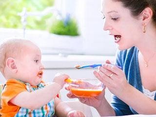 離乳食を自分で食べようとする赤ちゃん