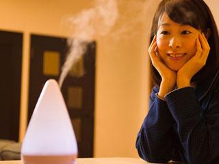 加湿器から出る蒸気を見る女性