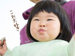 手づかみにした離乳食をおいしそうに食べる幼時