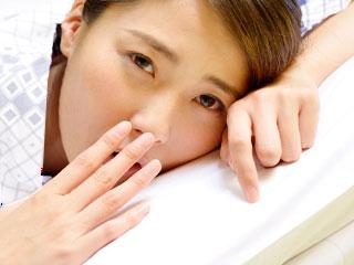 寝床で欠伸をする女性