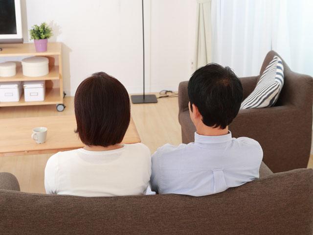 ソファに並んで座る夫婦