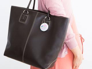 買物バッグを肩にかけた妊婦