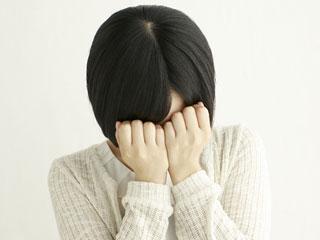 顔を両手で隠して落ち込む女性