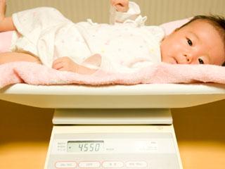 体重計にのせられた赤ちゃん