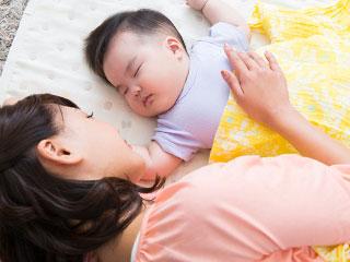 赤ちゃんを見守りながら添い寝する女性
